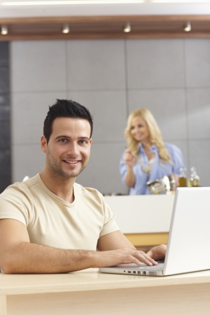 Happy young man using laptop computer at home, woman cooking at background. photo
