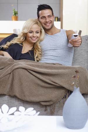 pareja viendo tv: Feliz pareja amorosa viendo la televisi�n en casa, sentado en el sof�, abrazando, usando el control remoto. Foto de archivo
