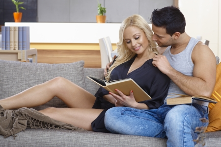 be kissed: Young loving couple sitting on sofa, woman reading book, man kissing her. Stock Photo