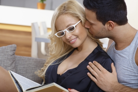 Young woman reading book at home, man kissing and embracing her. photo