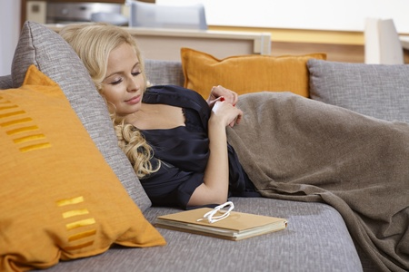 Attractive young woman lying on sofa, sleeping. Stock Photo - 19376972