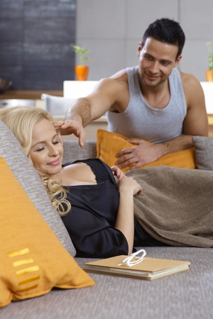 Young woman sleeping at home on sofa, man trying to wake her up, both smiling. Stock Photo - 19376985