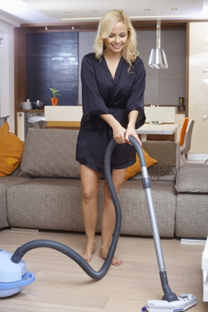 hoover: Pretty blonde girl in dressing gown using vacuum cleaner at home, smiling. Stock Photo