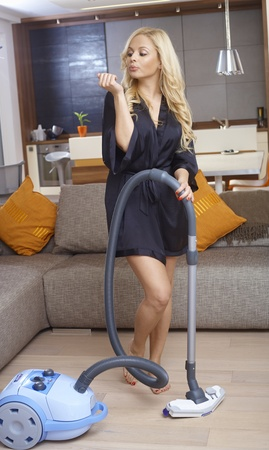 Pretty blonde woman in dressing gown using vacuum cleaner while blowing freshly polished nails. photo