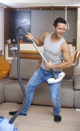 Young man using vacuum cleaner as guitar, having fun in living room. photo