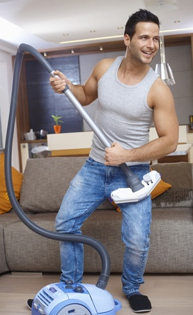 Young man holding vacuum cleaner as guitar, having fun at home, smiling. photo
