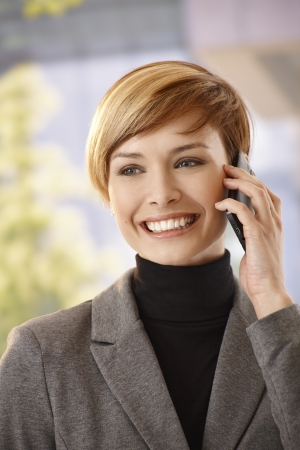 gingerish: Portrait of happy young businesswoman talking on mobile outdoor Stock Photo
