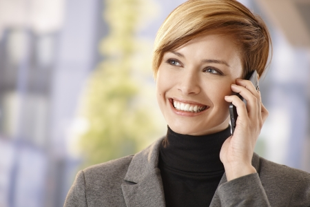 talking by phone: Outdoor portrait of happy businesswoman talking on mobile phone, smiling. Stock Photo