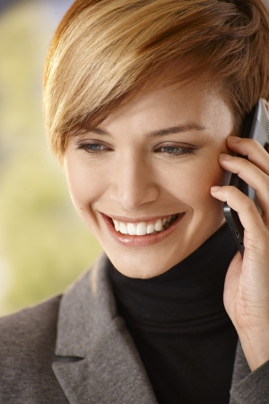 Closeup portrait of happy young woman talking on mobile phone photo