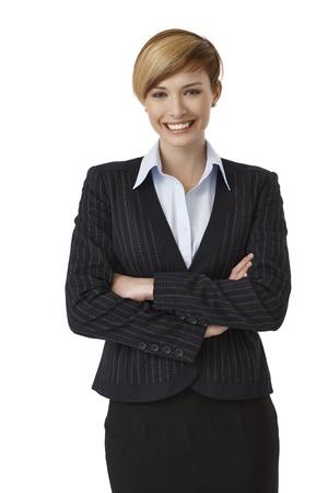 mani incrociate: Ritratto di fiduciosa giovane imprenditrice in piedi con le mani incrociate su sfondo bianco.