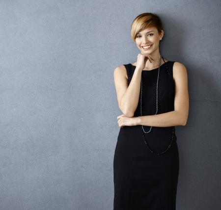 Schöne junge Frau im Cocktail-Kleid auf grauem Hintergrund
