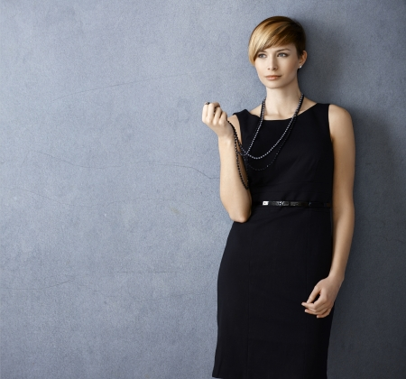black dress: Attractive young woman wearing black dress and pearl necklace on grey background