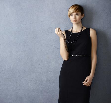 gingerish: Mujer joven y atractiva con un vestido negro y un collar de perlas sobre fondo gris
