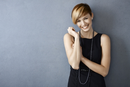 Portrait of happy young woman in black dress and pearls on grey background Stock Photo