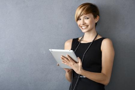 Portrait de jeune femme élégante en robe noire aide de la tablette au mur penché Banque d'images