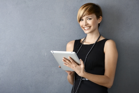 Portrait of elegant young woman in black dress using tablet leaning to wall photo