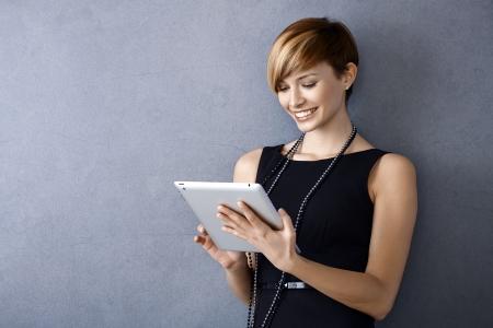 화면을보고, 벽에 기대어 태블릿을 사용하여 우아한 젊은 사업가