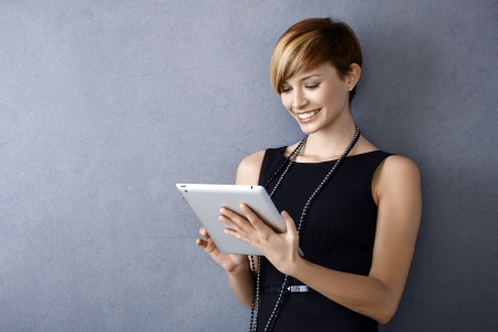 Elegant young businesswoman using tablet leaning to wall, looking at screen photo