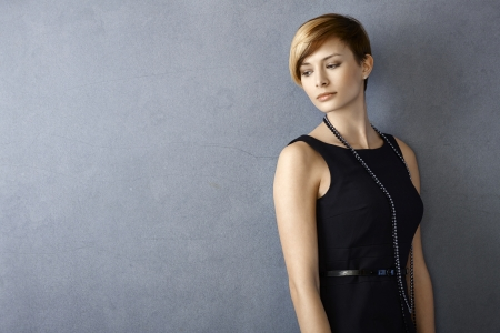 gingerish: Portrait of dreamy young woman in black dress leaning to wall Stock Photo