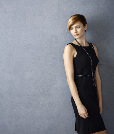 fantasize: Portrait of serious young woman in black dress leaning to wall Stock Photo
