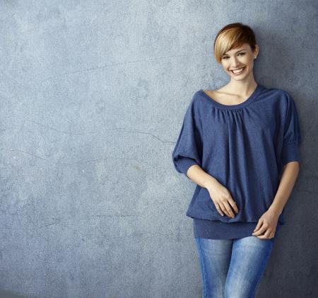 Aantrekkelijke jonge vrouw in blauwe jeans leunend tegen de muur, glimlachen Stockfoto - 19501922