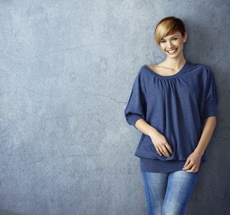 Attractive young woman in blue jeans leaning against wall, smiling photo