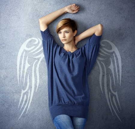 Attractive woman with angel wing illustration standing against grey wall illustration