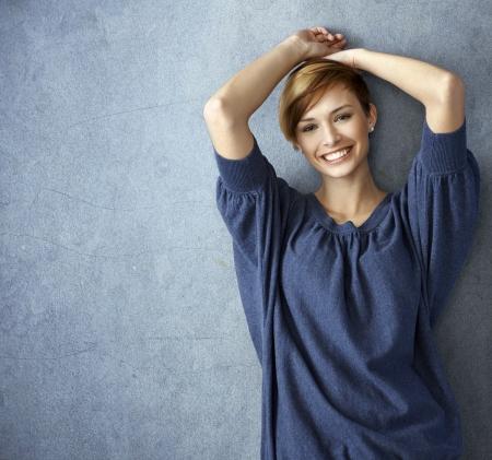 청바지에 행복 한 젊은 여자 웃 고, 벽에 기대어