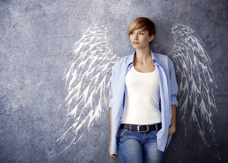 conceptual image: Attractive woman with angel wing illustration standing against grey wall