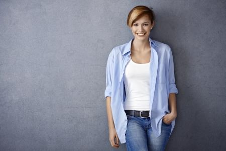 ropa casual: Mujer joven feliz en ropa casual, sonriendo