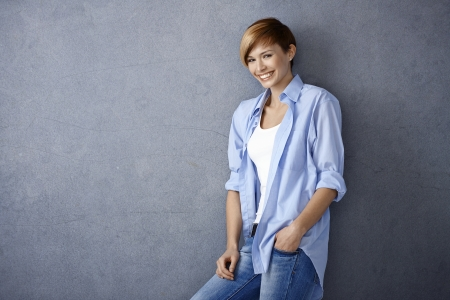 Happy young woman in casual clothes leaning to wall smiling Stock Photo