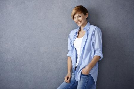 gingerish: Mujer joven feliz en ropa casual apoy�ndose a la pared sonriendo
