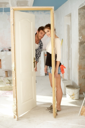 Young couple looking through door frame in home under construction.