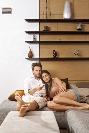 man couch: Young attractive couple sitting on sofa at home, watching tv.