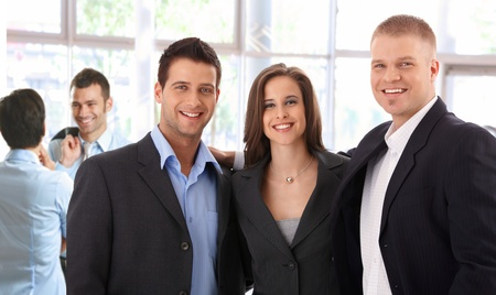 Portrait of successful young business team standing at bright office, smiling happy photo