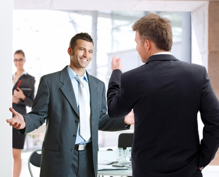 outspreading: Young businessmen talking at meetingroom, smiling happy.