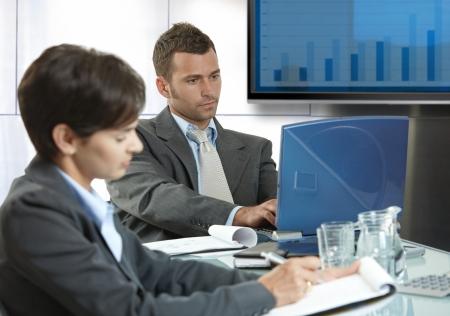 Businesspeople sitting around table at meetingroom, working. photo