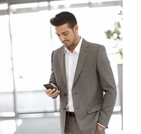 iş adamı: Genç işadamı mobilephone kullanarak, ofis binası ayakta.