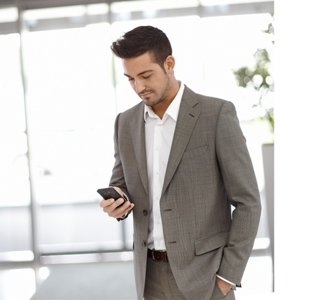 sms text: Young businessman standing at office building, using mobilephone.