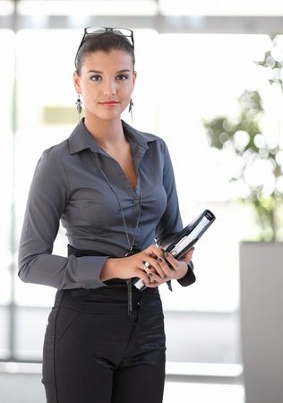 Office portrait of attractive young businesswoman with personal organizer, looking at camera. photo