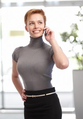 gingerish: Bastante joven mujer de negocios hablando por tel�fono m�vil en el edificio de oficinas.