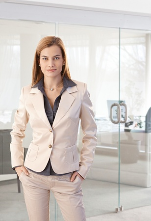 Portrait of trendy businesswoman at office, smiling with hands in pockets. photo