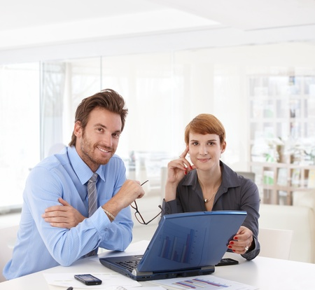 Young businesspeople working at bright office, using laptop computer, smiling happy. Stock Photo - 19876072