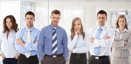 Photo d'équipe de la réussite des jeunes gens confiants permanent au bureau.