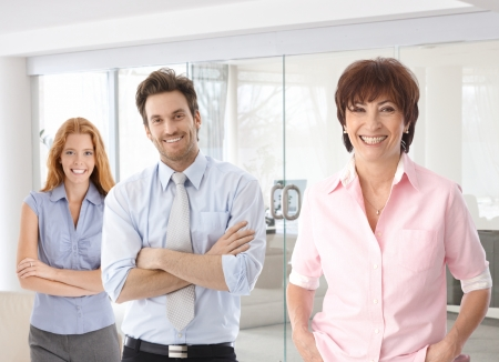 Senior businesswoman and young colleagues smiling happy at office.