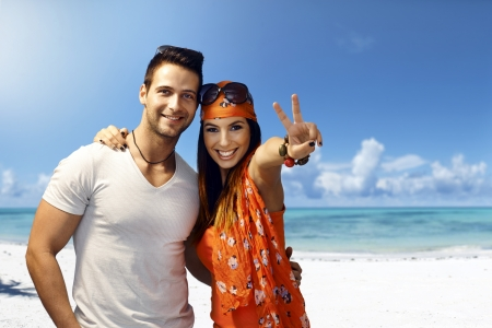 Happy young couple embracing on the beach, smiling, showing victory sign.
