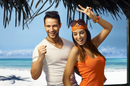Happy young couple dancing on tropical beach at summer holiday.