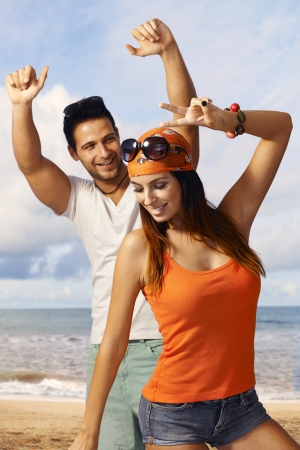 beach clothes: Happy young couple enjoying summer holiday on the beach, dancing, having fun. Stock Photo