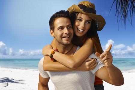 novio: Feliz pareja amorosa a cuestas en la playa tropical en verano, sonriente, mirando a otro lado. Foto de archivo