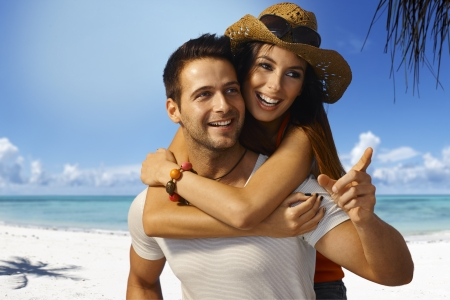 Happy loving couple piggyback on tropical beach at summertime, smiling, looking away.